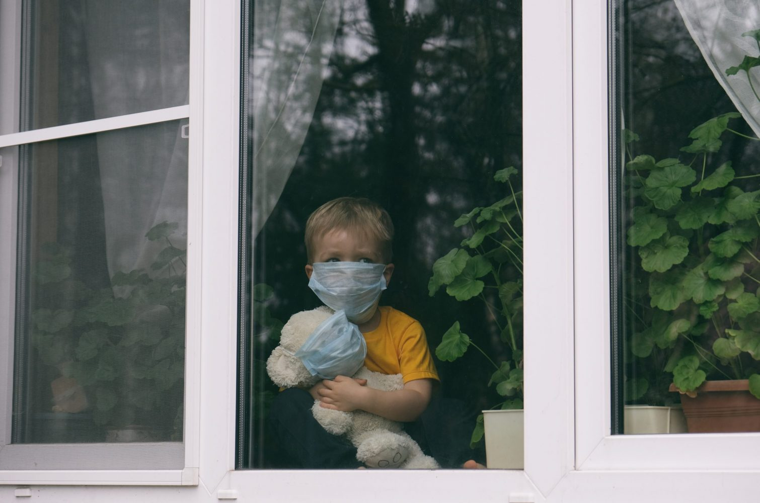 Boy watching out window with mask